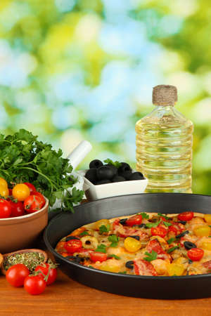 colorful composition of delicious pizza, vegetables and spices on wooden background close-up photo