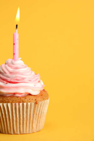 cake with icing: tasty birthday cupcake with candle, on yellow background