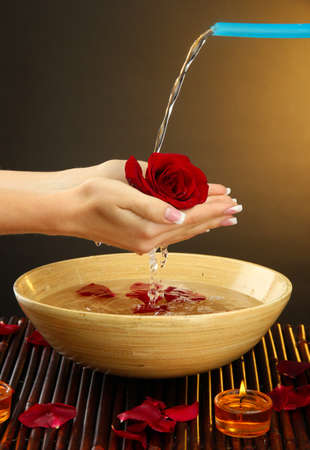 feminine hands: woman hands with wooden bowl of water with petals, on brown background
