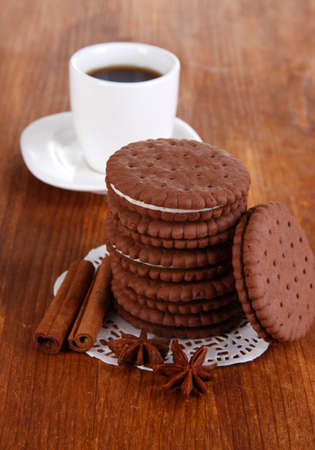 Chocolate cookies with creamy layer and cup of coffe on wooden table close-up photo