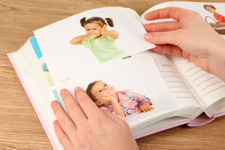 Photos in hands and photo album on wooden table Stock Photo - 19360554