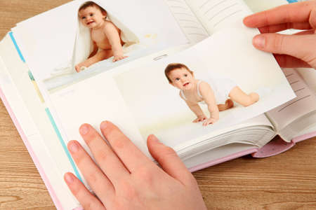 Photos in hands and photo album on wooden table Stock Photo - 19360549