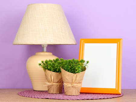 Colorful photo frame, lamp and flowers on wooden table on lilac background photo