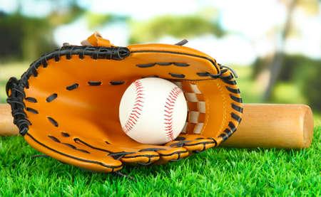 guante de beisbol: Guante de béisbol, un bate y una pelota en la hierba en el parque