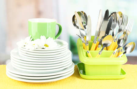 Plates, forks, knives, spoons and other kitchen utensil on color napkin, on bright background Stock Photo - 18800959