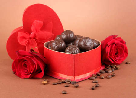 Chocolate candies in gift box, on brown background photo
