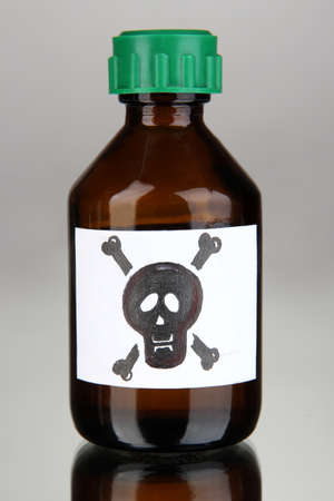 deadly poison: Deadly poison in bottle on grey background Stock Photo