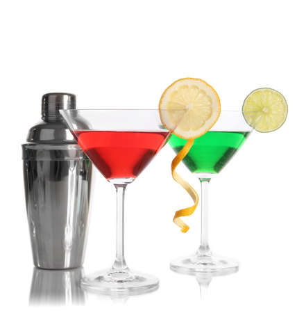 Alcoholic cocktails in martini glasses with shaker isolated on white photo