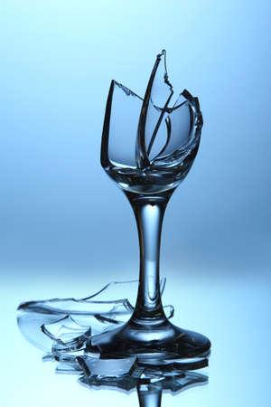 Broken wineglass on blue background photo