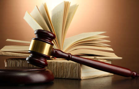 verdicts: wooden gavel and books on wooden table,on brown background