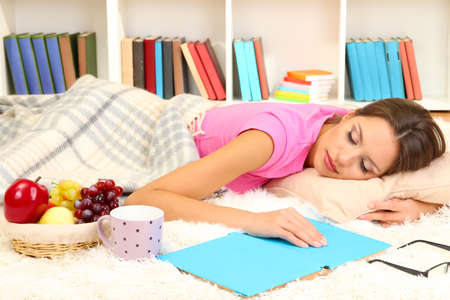 Young female asleep while reading book on floor photo
