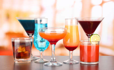 Several glasses of different drinks on bright background photo