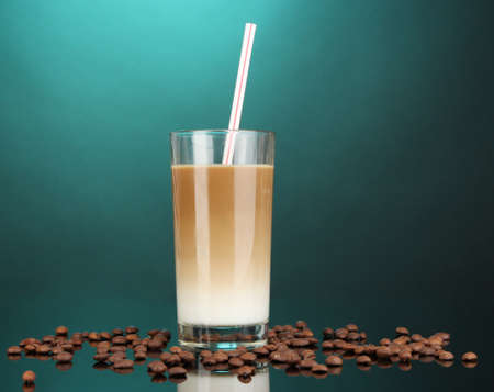 Cold coffee with ice in glass on color background photo
