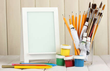 Photo frame as easel with artists tools on wooden background photo