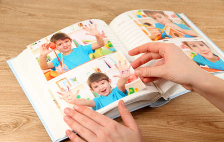 Photos in hands and photo album on wooden table Stock Photo - 19360591