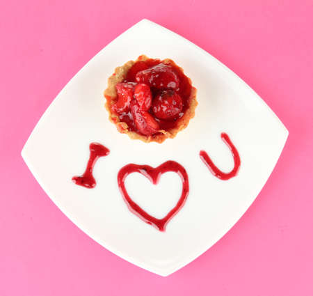 Sweet cake with strawberry and sauce on plate, on color background photo