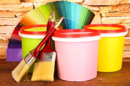 Set for painting: paint pots, brushes, palette of colors on stone wall background photo