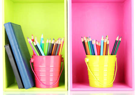 Colorful pencils in pails with writing-pad on shelves photo
