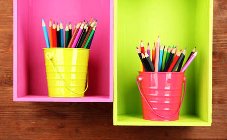 Colorful pencils in pails on shelves on wooden background photo