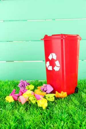 degradable: Recycling bin with papers on grass on light blue background