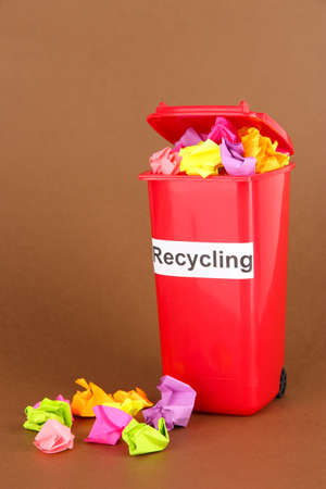 Recycling bin with papers on brown background photo