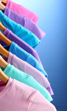 Lots of T-shirts on hangers on blue background Stock Photo - 18892002