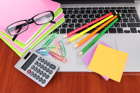 Laptop with stationery on table photo