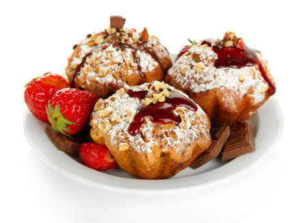 Tasty muffin cakes with strawberries and chocolate on plate, isolated on white photo