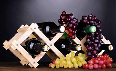Bottles of wine placed on wooden stand on grey background photo