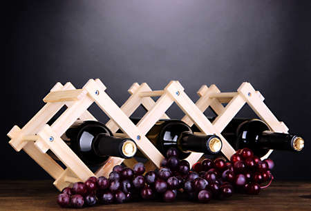 Bottles of wine placed on wooden stand on grey background Stock Photo - 18891991