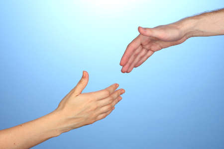 Womens hand goes to the mans hand on blue background Stock Photo