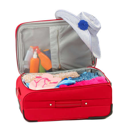 Suitcase with summer clothes, a hat and suntan isolated on white photo