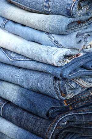 Many jeans stacked in a pile closeup photo