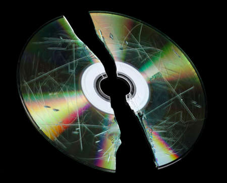 defective: Defective and broken disk with information isolated on black Stock Photo