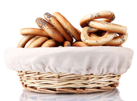 tasty bagels in basket, isolated on white photo