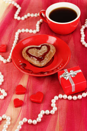 Chocolate cookie in form of heart with cup of coffee on pink tablecloth close-up photo
