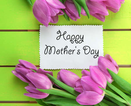 mothers group: Beautiful bouquet of purple tulips and card on green wooden background