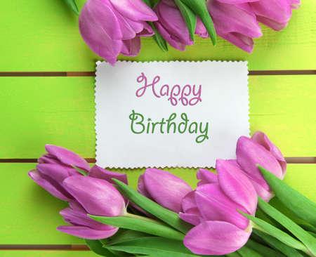 flores de cumpleaños: Hermoso ramo de tulipanes morados y tarjeta verde sobre fondo de madera Foto de archivo