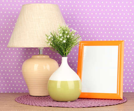 Colorful photo frame, lamp and flowers on wooden table on lilac polka dots background Stock Photo
