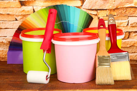 Set for painting: paint pots, brushes, paint-roller, palette of colors on stone wall background photo