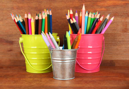 hued: Colorful pencils in three pails on wooden background Stock Photo