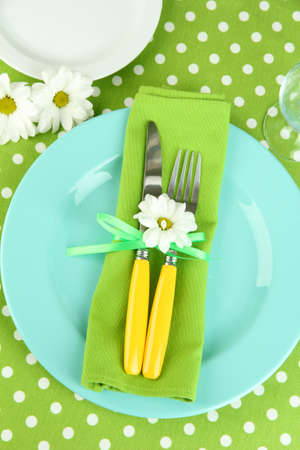 Knife and fork wrapped in napkin, on plate, on color tablecloth  background Stock Photo - 19040420