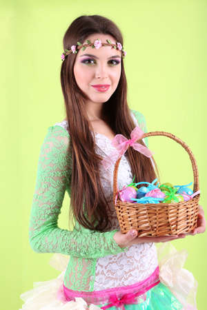 Happy female holding basket with Easter eggs, on green background photo
