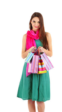 Young beautiful girl in green dress with pink scarf holding bright bags, isolated on white