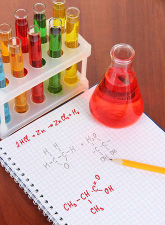 Test tubes with colorful liquids and formulas on table photo