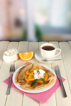 Pancakes with orange on bright background photo