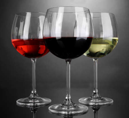 stemware: Assortment of wine in glasses on grey background Stock Photo