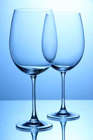 stemware: Empty wine glasses arranged on blue background