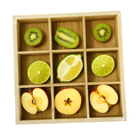 Sliced fruit in wooden box isolated on white photo
