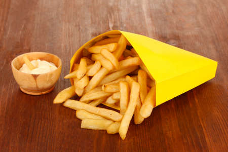 French fries in paper bag on wooden table close-up photo